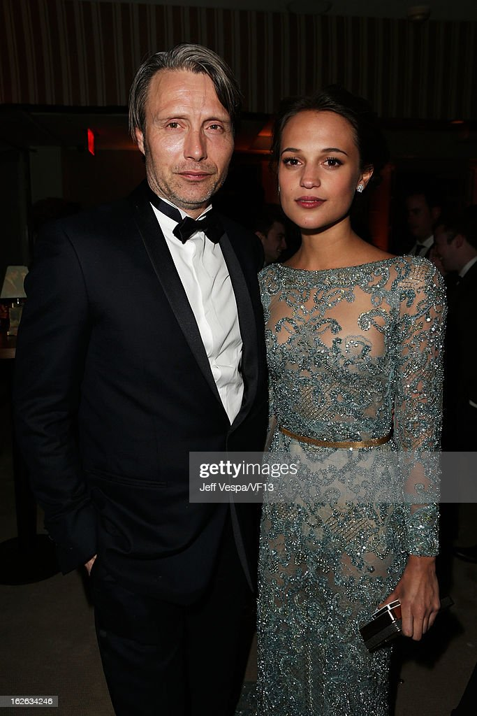Actors Mads Mikkelsen (L) and Alicia Vikander attend the 2013 Vanity Fair Oscar Party hosted by Graydon Carter at Sunset Tower on February 24, 2013 in West Hollywood, California.