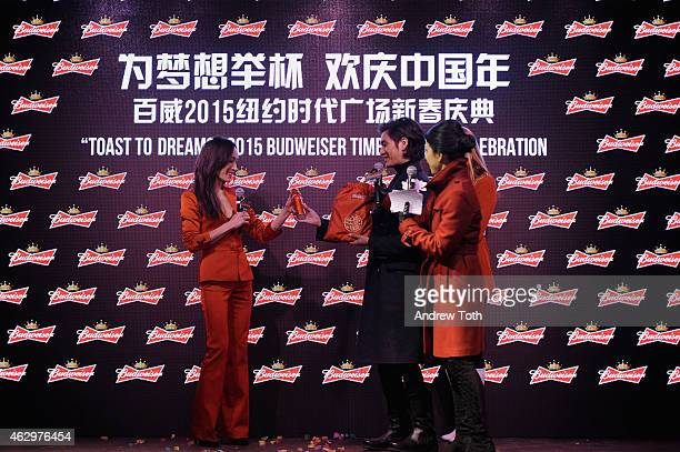Actors Maggie Q and Chen Kun speak on stage during Maggie Q toasts the Chinese New Year at Times Square on February 7 2015 in New York City