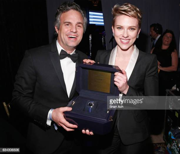 Actors Mark Ruffalo and Scarlett Johansson wearing Harry Winston poses with a Harry Winston timepiece presented with her amfAR Award of Courage...