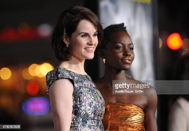 Actors Michelle Dockery and Lupita Nyong'o arrive at the Los Angeles premiere of 'NonStop' at Regency Village Theatre on February 24 2014 in Westwood...
