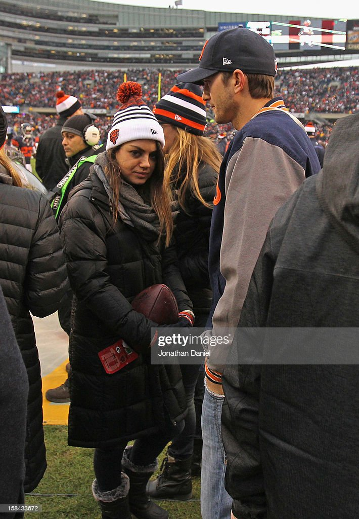 Actors Mila Kunis and Ashton Kutcher stand on the sidleines before the Chicago Bears take on the Green Bay Packers at Soldier Field on December 16, 2012 in Chicago, Illinois. The Packers defeated the Bears 21-13.