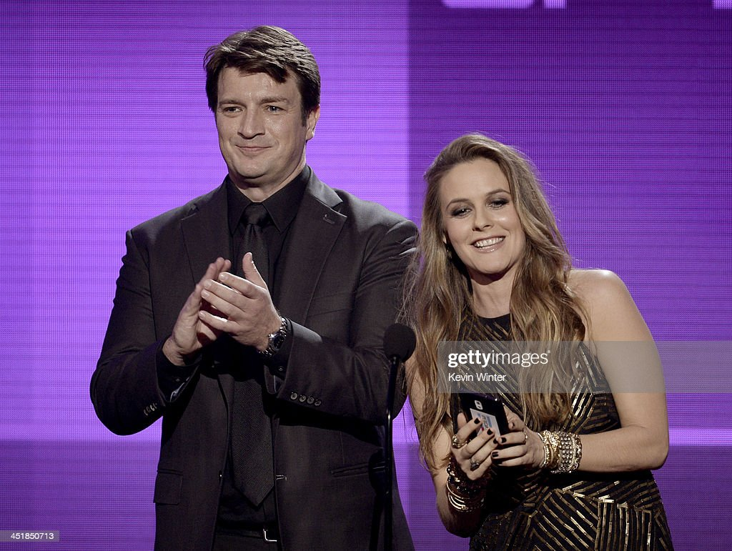 Actors <a gi-track='captionPersonalityLinkClicked' href=/galleries/search?phrase=Nathan+Fillion&family=editorial&specificpeople=834463 ng-click='$event.stopPropagation()'>Nathan Fillion</a> and <a gi-track='captionPersonalityLinkClicked' href=/galleries/search?phrase=Alicia+Silverstone&family=editorial&specificpeople=202861 ng-click='$event.stopPropagation()'>Alicia Silverstone</a> speak onstage during the 2013 American Music Awards at Nokia Theatre L.A. Live on November 24, 2013 in Los Angeles, California.