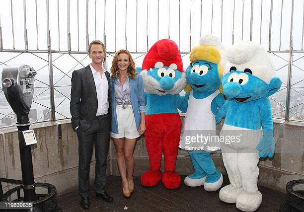 Actors Neil Patrick Harris and Jayma Mays pose with actors wearing Smurf costumes visit the The Empire State Building on July 25 2011 in New York City