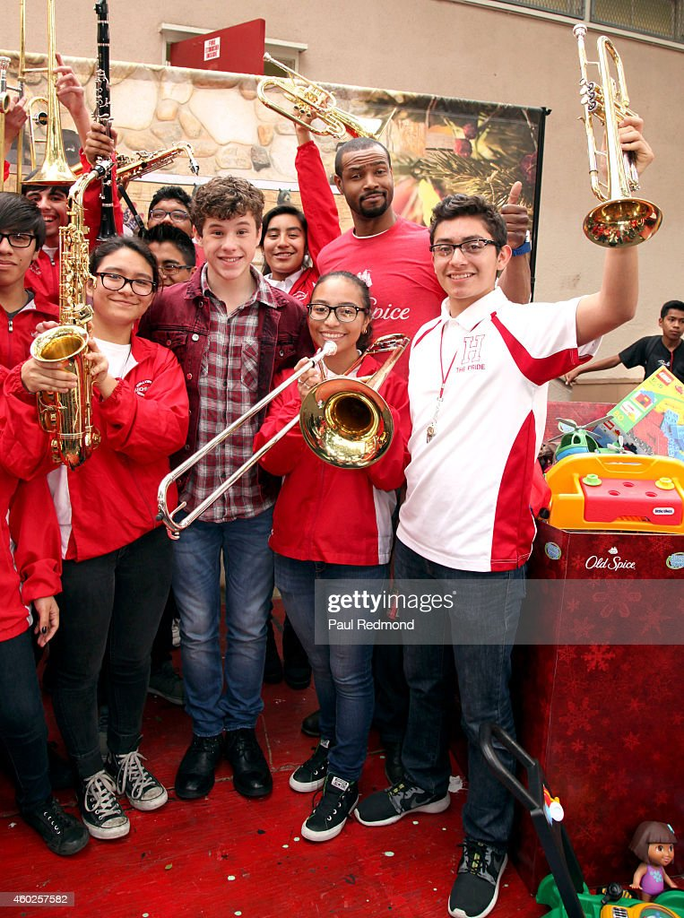Actors Nolan Gould (C) and Isaiah Mustafa (second from R) pose with Hollywood High School Marching Band at the Inaugural Old Spice Holispray Holiday Toy Donation and Exchange Benefit for Second Chance Toys at Hollywood High School on December 10, 2014 in Los Angeles, California.