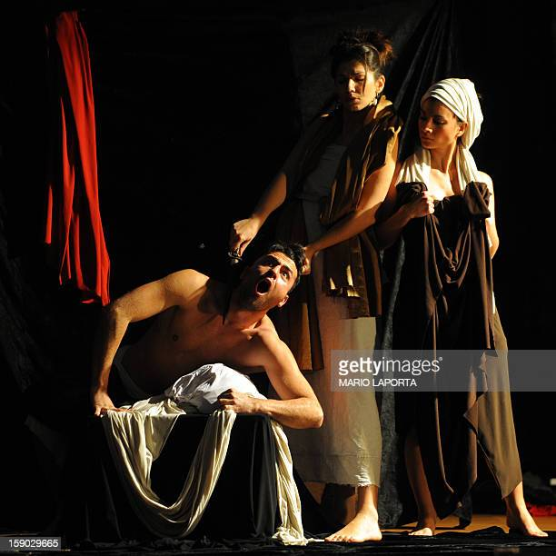 Actors of the 'Ludovica Carambelli Theater' company perform as they form a representation of Caravaggio's painting 'Giuditta e Oloferne' during the...
