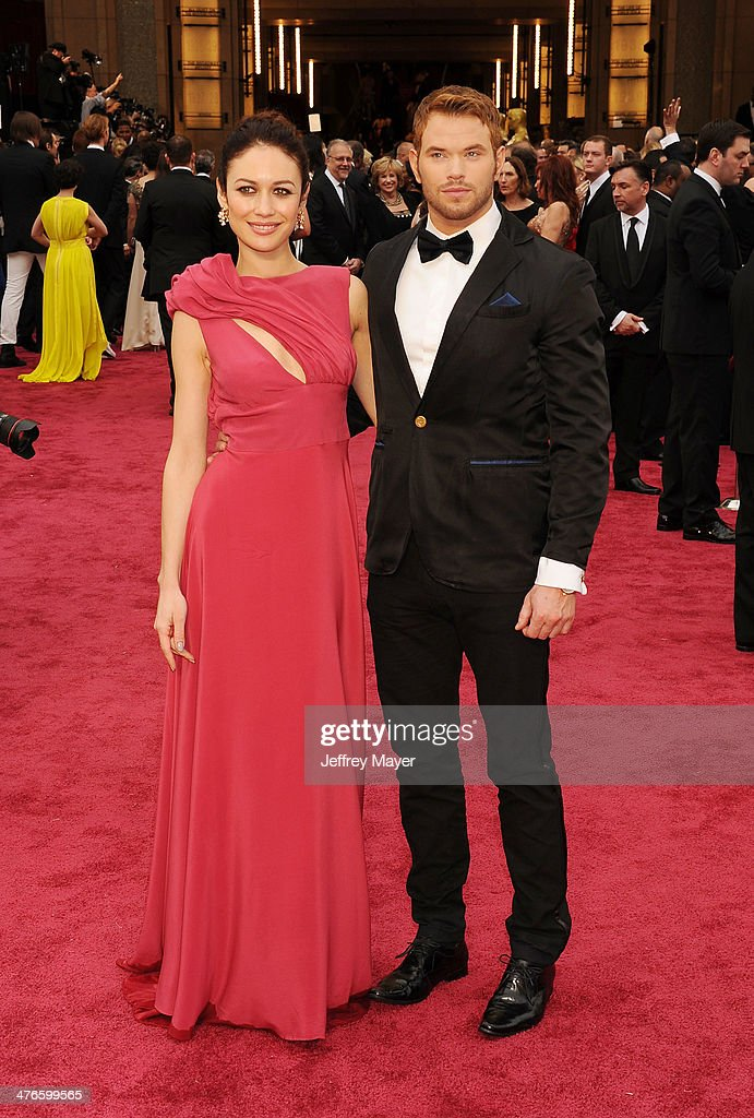 Actors Olga Kurylenko (L) and Kellan Lutz attend the 86th Annual Academy Awards held at Hollywood & Highland Center on March 2, 2014 in Hollywood, California.