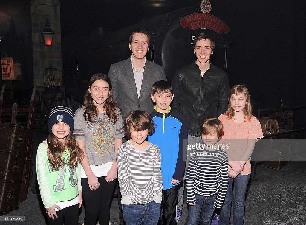 Actors Oliver Phelps and James Phelps (center) pose with fans at The Harry Potter Exhibit at Discovery Times Square on February 19, 2013 in New York City.