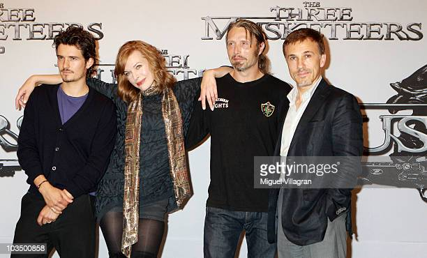 Actors Orlando Bloom Milla Jovovich Mads Mikkelsen and Christoph Waltz pose during a photocall to promote the movie The Three Musketeers on August 20...