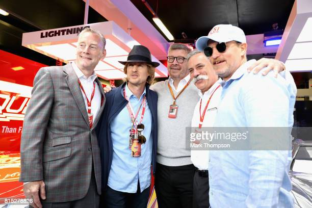 Actors Owen Wilson and Woody Harrelson pose for a photo with Sean Bratches Managing Director of the Formula One Group Chase Carey CEO and Executive...