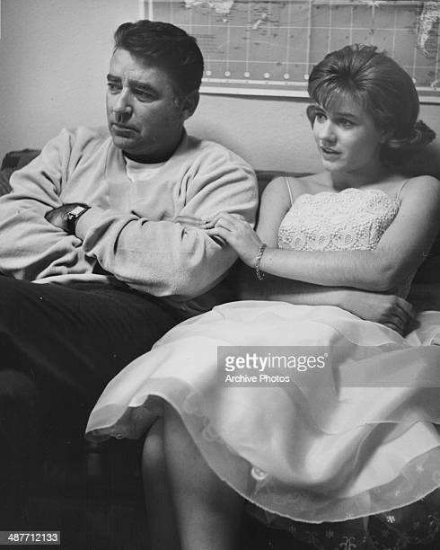 Actors Peter Lawford and Patty Duke sitting next to each other and holding hands on the set of the The Patty Duke Show 1964