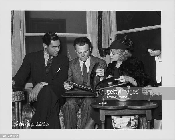 Actors Phillip Reed James Cagney and Joan Blondell looking through a photo album together 1935