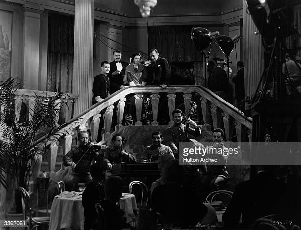 Actors Ramon Novarro Jean Hersholt and Helen Chandler watching a band with director Jacques Feyder on the set of the MGM film 'Daybreak'