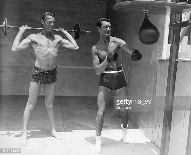 Actors Randolph Scott and Cary Grant show off their athletic prowess Scott lifts weights while Grant punches at a speedbag Undated photograph