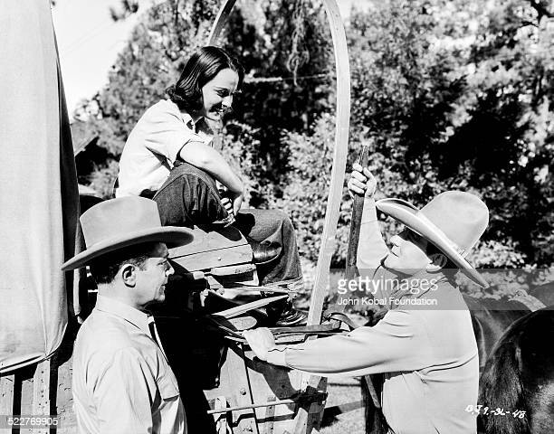 Actors Ray Corrigan Louise Brooks and John Wayne on the set of the movie 'Overland Stage Raiders' for Republic Pictures 1938