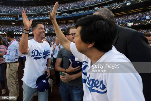 Actors Rob Lowe and Ken Jeong highfive prior to Game 1 of the 2017 World Series between the Houston Astros and the Los Angeles Dodgers at Dodger...