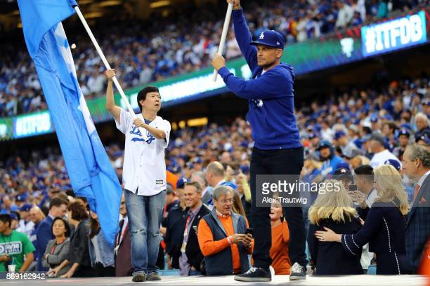 Actors Rob Lowe and Ken Jeong wave Dodger flags on top prior to Game 7 of the 2017 World Series between the Houston Astros and the Los Angeles...