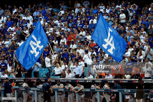 Actors Rob Lowe and Ken Jeong wave Dodgers flags on top of the Astros dugout prior to Game 1 of the 2017 World Series between the Houston Astros and...