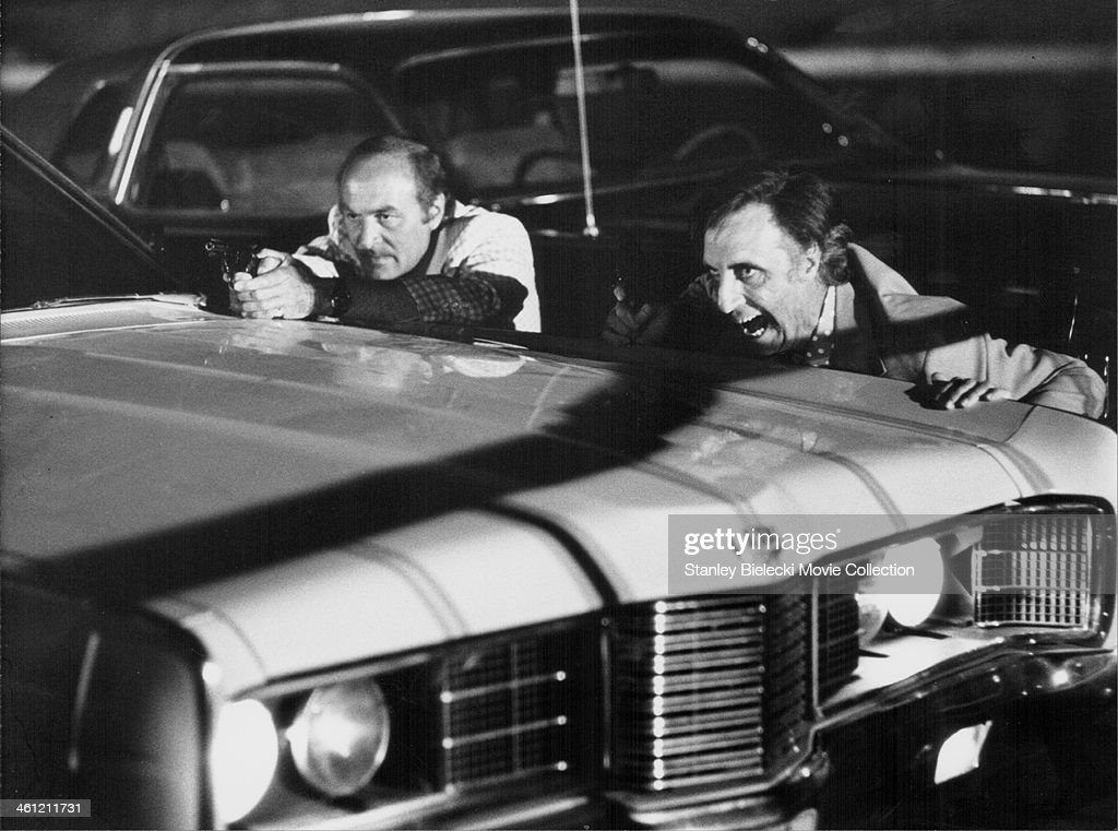 Actors Robert Loggia and Timothy Carey hiding behind a car during a shootout in a scene from the movie 'Speedtrap' 1977