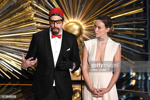 Actors Sacha Baron Cohen and Olivia Wilde speak onstage during the 88th Annual Academy Awards at the Dolby Theatre on February 28 2016 in Hollywood...