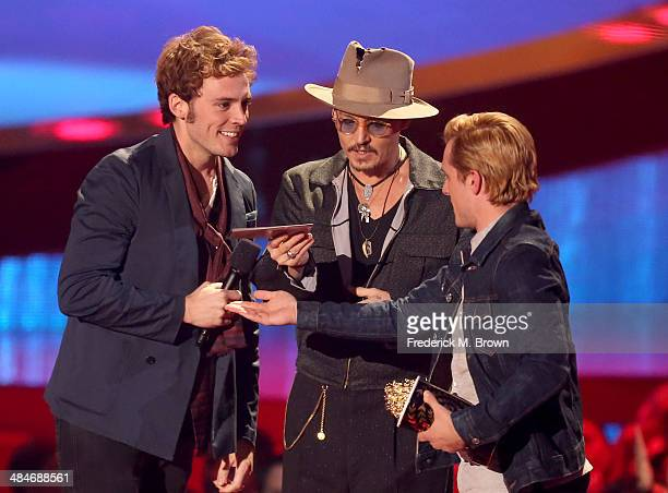 Actors Sam Claflin and Josh Hutcherson accept the Movie of the Year award for 'The Hunger Games Catching Fire' from actor Johnny Depp onstage at the...