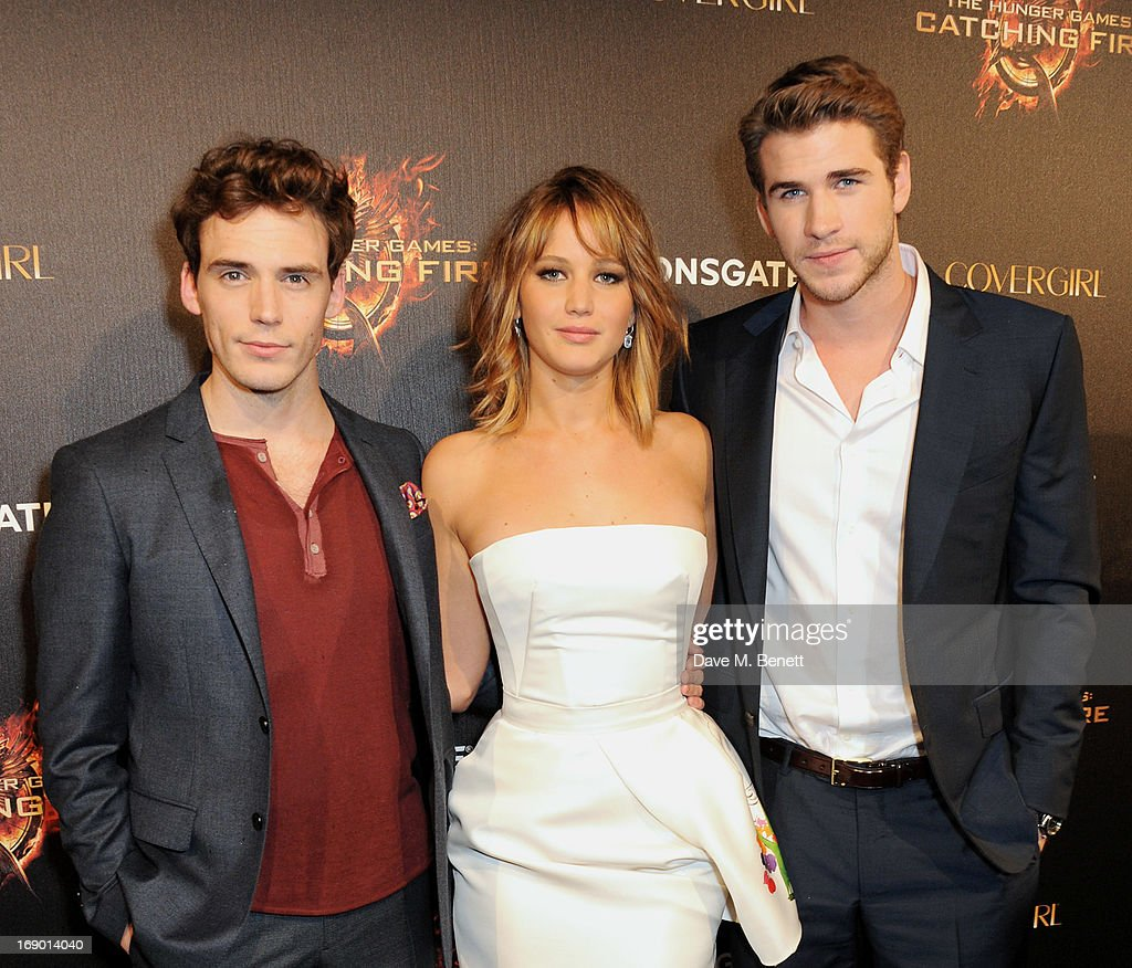 Actors Sam Claflin, Jennifer Lawrence and Liam Hemsworth arrive on the Red Carpet at Lionsgate's 'The Hunger Games: Catching Fire' Cannes Party at Baoli Beach sponsored by COVERGIRL on May 18, 2013 in Cannes, France.