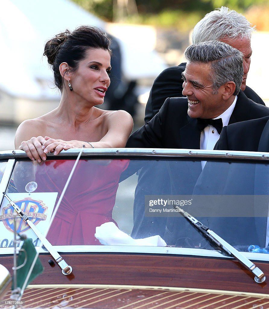 Actors <a gi-track='captionPersonalityLinkClicked' href=/galleries/search?phrase=Sandra+Bullock&family=editorial&specificpeople=202248 ng-click='$event.stopPropagation()'>Sandra Bullock</a> and <a gi-track='captionPersonalityLinkClicked' href=/galleries/search?phrase=George+Clooney&family=editorial&specificpeople=202529 ng-click='$event.stopPropagation()'>George Clooney</a> are seen joking with each other as they arrive by boat for the 'Gravity' Premiere And Opening Ceremony Red Carpet on day 1 of the 70th Venice International Film Festival on August 28, 2013 in Venice, Italy.