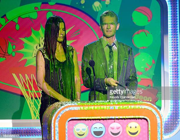Actors Sandra Bullock and Neil Patrick Harris get slimed as they speak onstage during Nickelodeon's 26th Annual Kids' Choice Awards at USC Galen...