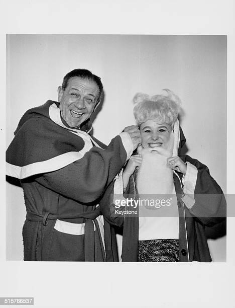 Actors Sid James and Barbara Windsor laughing as they wear Santa Claus costumes at the Christmas luncheon of the Variety Club of Great Britain Savoy...
