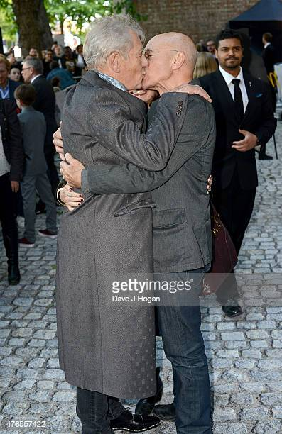 Actors Sir Ian McKellen and Patrick Stewart kiss as they attend the UK Premiere of 'Mr Holmes' at the Odeon Kensington on June 10 2015 in London...