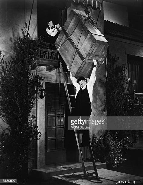 Actors Stan Laurel and Oliver Hardy attempt to lower a large wooden crate containing a player piano down a ladder in a still from the film 'The Music...