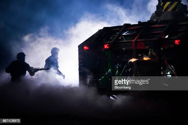 Actors stand amid smoke on a stage near a 'cage' for the Fiat Chrysler Automobiles NV 2018 Dodge Challenger SRT Demon sports vehicle during an event...