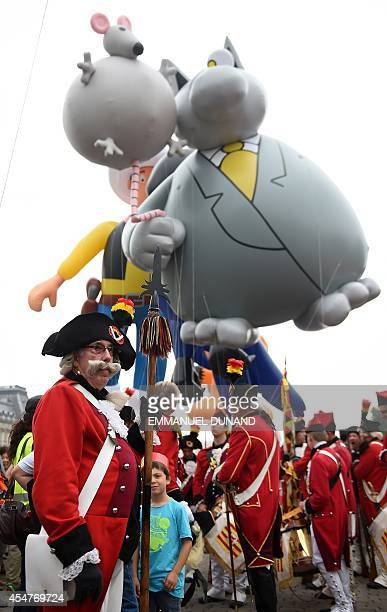Actors stand next to an inflatable of Belgian comic strip character Le Chat during the Balloon's Day Parade as part of the annual Comic Book Festival...