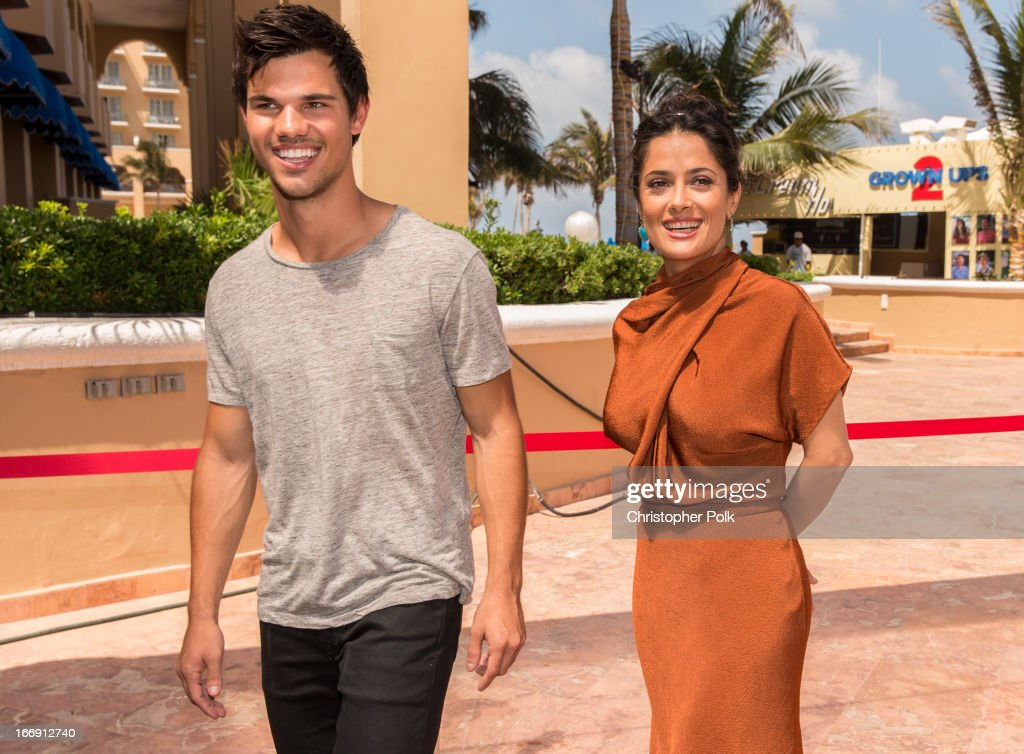 Actors <a gi-track='captionPersonalityLinkClicked' href=/galleries/search?phrase=Taylor+Lautner&family=editorial&specificpeople=228959 ng-click='$event.stopPropagation()'>Taylor Lautner</a> and <a gi-track='captionPersonalityLinkClicked' href=/galleries/search?phrase=Salma+Hayek&family=editorial&specificpeople=201844 ng-click='$event.stopPropagation()'>Salma Hayek</a> attend 'Grown Ups 2' Photo Call at The 5th Annual Summer Of Sony at the Ritz Carlton Hotel on April 18, 2013 in Cancun, Mexico.