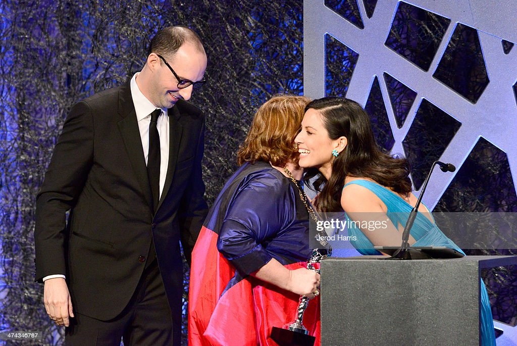 Actors Tony Hale (L) and Olivia Munn (R) present the award for Excellence in Costume Design for Contemporary Film, Blue Jasmine to winner Suzy Benzinger (C) onstage during the 16th Costume Designers Guild Awards with presenting sponsor Lacoste at The Beverly Hilton Hotel on February 22, 2014 in Beverly Hills, California.