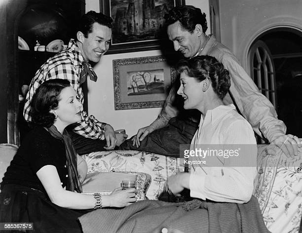 Actors Vivien Leigh John Tullis Peter Finch and Rachel Kempson chatting at a home of Sir Laurence and Lady Olivier prior to attending a square dance...