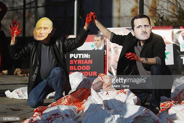 Actors wearing masks of Syrian President Bashar alAssad and Russian Prime Minister Vladimir Putin perform with body bags during a demonstration...