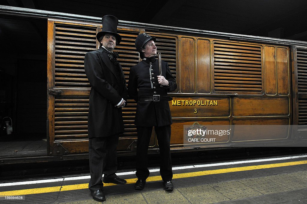 Actors wearing period costumes pose for photographers next to a steam train which used to carry passengers in the 19th century as it arrived at Moorgate Underground Station in central London on January 13, 2013, to mark 150 years since the first London underground journey. AFP PHOTO / CARL COURT