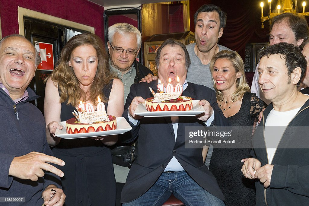 Actors Xavier Letourneur, Jessica Borio, Daniel Russo, Axelle Marine and Gerard Loussine, foreground, director Eric Civanyan, playwright and actor Jean-Francois Cros and playwright Sylvain Meyniac, background, pose with cakes celebrating the 100th performance of the play 'Hier Est Un Autre Jour' at Theatre des Bouffes Parisiens on May 11, 2013 in Paris, France.