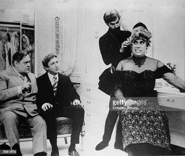 Actors Zero Mostel and Gene Wilder look on as Christopher Hewett is fitted in a woman's dress and hat in a still from the film 'The Producers'...