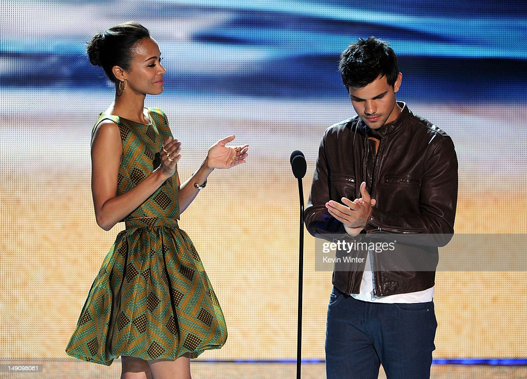 Actors Zoe Saldana (L) and Taylor Lautner speak onstage during the 2012 Teen Choice Awards at Gibson Amphitheatre on July 22, 2012 in Universal City, California.