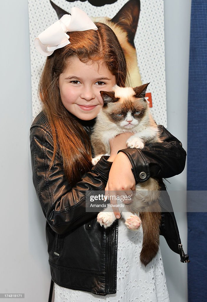 Actress Addison Riecke (L) and Grumpy Cat make an appearance at Kitson Santa Monica to promote Grump Cat's new book 'Grumpy Cat : A Grumpy Book' on July 23, 2013 in Santa Monica, California.