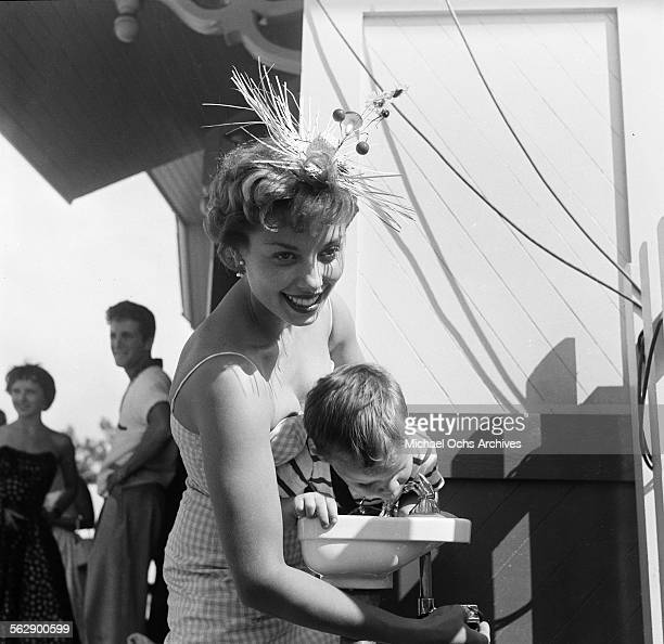 Actress Adelle August poses as she helps a young boy drink water during the Opening day of Disneyland in AnaheimCalifornia