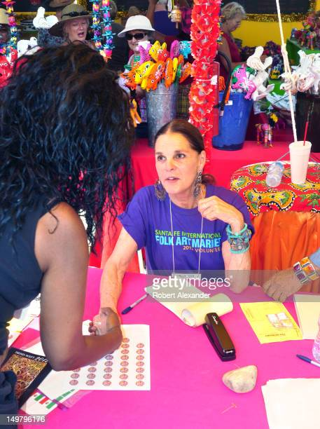 Actress Ali MacGraw shakes hands with one of her fans at the 2012 Santa Fe International Folk Art Market MacGraw was a volunteer salesperson at the...