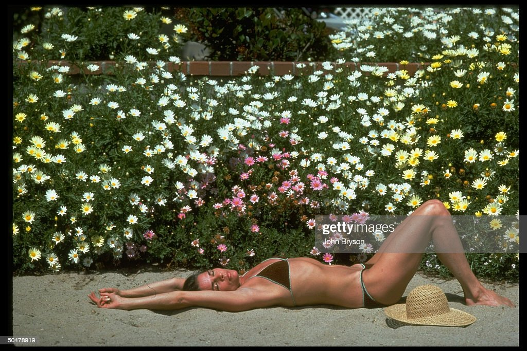 Actress Ali MacGraw wearing bikini stretched out on sand sun bathing.