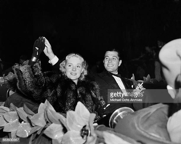 Actress Alice Faye with husband actor Tony Martin wave to a crowd during a parade in Los Angeles California