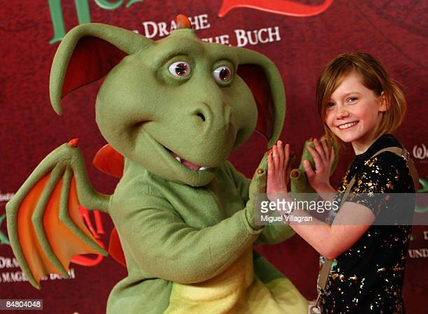 Actress Alina Freund poses for the media with Hector the dragon during the premiere of the movie 'Lilli The Witch The Dragon And The Magical Book' on...