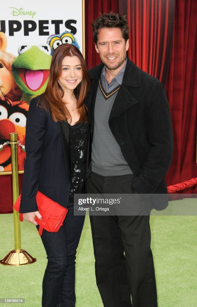 Actress Alyson Hannigan and actor Alexis Denisof arrive for 'The Muppets' Los Angeles Premiere held at the El Capitan Theatre on November 12, 2011 in Hollywood, California.