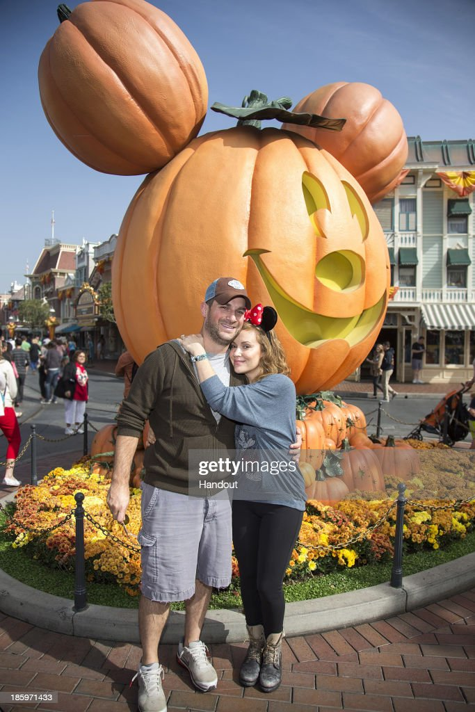 Actress Alyssa Milano of television series'Mistresses' and husband David Bugliari celebrate 'Halloween Time' at Disneyland on October 26, 2013 in Anaheim, California.