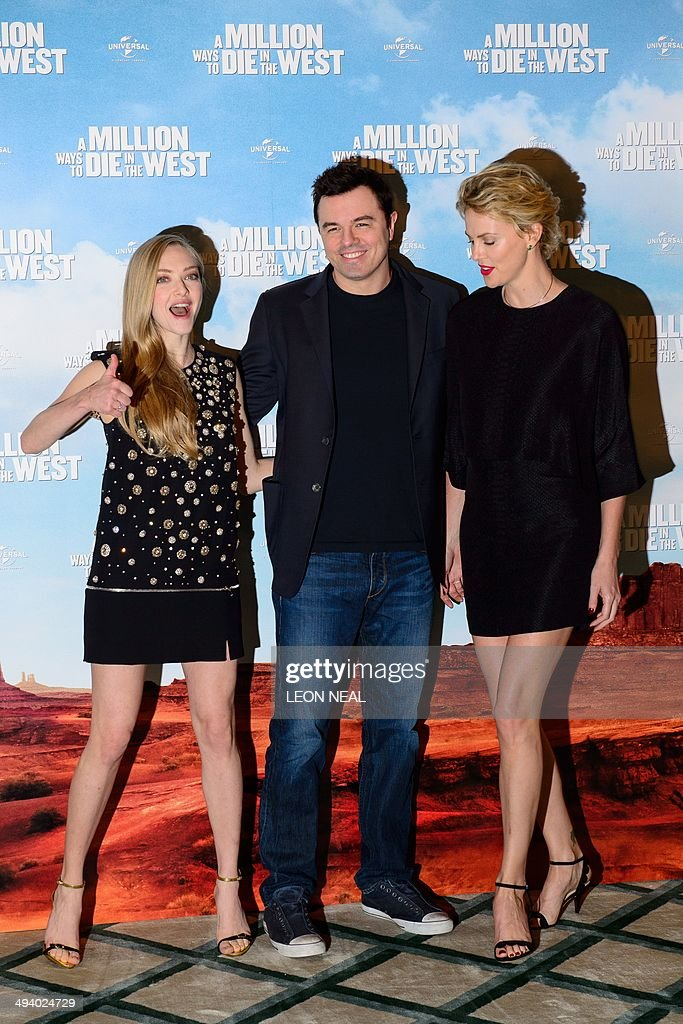 US actress Amanda Seyfried (L), US actor Seth MacFarlane and South African actress Charlize Theron pose for photographers during a photo call for their latest film 'A Million Ways To Die In The West' at Claridges, central London, on May 27, 2014. Starring Seth MacFarlane, Liam Neeson, Amanda Seyfried and Charlize Theron, the film is about a man in America's Wild West who has struggles to regain his courage after backing out of a gunfight. AFP PHOTO/LEON NEAL