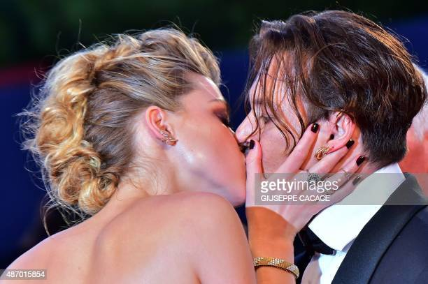 US actress Amber Heard kisses her husband US actor Johnny Depp as they arrive for the screening of the movie 'The Danish Girl' presented in...